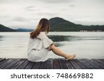 lonely woman sitting on wooden... | Shutterstock . vector #748669882
