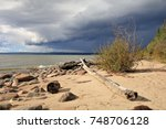 Beach at the shore of lesser slave lake in Autumn, Alberta in Canada. A dramatic cloud forms in the north of the lake.