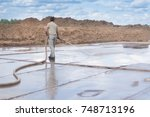 A Man With A Hose Washes The...