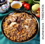 Small photo of Pilaf is Devzira. Rice red variety,mutton,mutton fat,onions,carrots,spices.On the table laid in the kicks slide with tea and salad..Uzbek national dish.The horizontal projection of the.