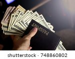 Small photo of money in a passport, a lot of dollars in hand, capital for travel, savings, emigration