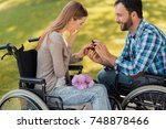 Small photo of A man and a woman in wheelchairs met in the park. A man makes a woman a prepossess. She is delighted with such a surprise. They are in a beautiful green park.