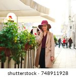 cute girl in a coat and purple... | Shutterstock . vector #748911928