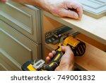 adjusting fixing cabinet door... | Shutterstock . vector #749001832