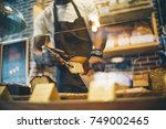 black man works in pastry shop. | Shutterstock . vector #749002465