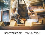 black man works in pastry shop. | Shutterstock . vector #749002468