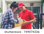 young man delivering package to ... | Shutterstock . vector #749074336