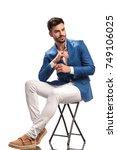 seated elegant man fixing his... | Shutterstock . vector #749106025
