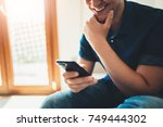 young happy smiling man using... | Shutterstock . vector #749444302