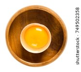 Small photo of Open raw chicken egg with yolk and white in its shell in a wooden bowl. Common food and versatile ingredient used in cooking. Isolated macro food photo close up from above on white background.