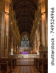 Small photo of Sydney, Australia - March 23, 2017: Chancel with purple-dressed altar, gothic tabernacle, white statues, and large stained window in back. Rather dark alcove like setting. Benches and pulpit in front.