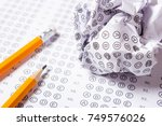 Small photo of Blank multiple choice answer sheet empty with pencil and spoiled answers compressed into a ball