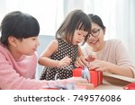 happy asian family wrapping a... | Shutterstock . vector #749576086