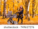 young mother with a stroller... | Shutterstock . vector #749617276