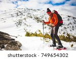 mountaineer in snowshoes carry... | Shutterstock . vector #749654302