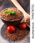 Small photo of Bowl of buckwheat kasha on wooden table.