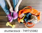 woman tying shoelaces with bag... | Shutterstock . vector #749715382