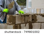Small photo of Builder erects a wall erection of blocks