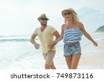 active couple on the beach | Shutterstock . vector #749873116