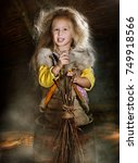 Small photo of Girl shows fantastic character, fantastic character grandma ezhka, girl in a mortar with a broom