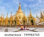 family burmese people  praying respects at Shwedagon big golden pagoda most sacred Buddhist pagoda in rangoon, Myanmar(Burma) on blue sky background