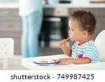 little baby eating puree indoors | Shutterstock . vector #749987425