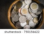 Small photo of Thai Baht Coins Macro Close Up in Wood Container with King of Thailand on obverse and Wat Arun on reverse. Ring made of Cupronickel and Center of Aluminium Bronze. Dark Vignette Money Background