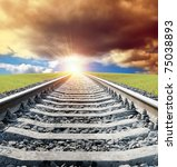 rail goes to sun in dramatic sky - stock photo