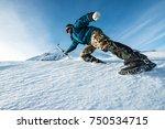 climber with an ice ax climb on ... | Shutterstock . vector #750534715