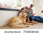 Stock photo father reading book with son and daughter and pet dog at home 750828436