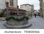 "Small photo of Carcassonne, France, December 25, 2015, cistern decorated for Christmas in the middle of a Carcassonne street. A man walking with a cane walks away. In the distance you see a poster of ""Bonas Festas"""