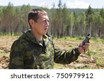 Small photo of Finding a position using a gps device. A forest warden standing on the hillside and looking in the navigation on the GPS in the background a field of a forest nursery with plantings of pine and cedar