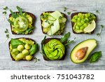 Small photo of Fresh avocado toasts with different toppings. Healthy vegetarian breakfast with rye wholegrain sandwiches
