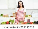 beautiful young woman cooking... | Shutterstock . vector #751199812