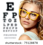 beautiful blond woman with yellow trendy glasses on the background of eye test chart - stock photo