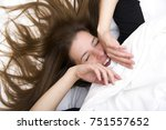 Small photo of Funny wakening. Young woman is lying in her bed, smiling and joking. Lifestyle concept.