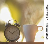 black alarm clock and a cup of... | Shutterstock . vector #751623352