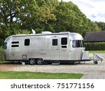 Small photo of Wareham, Dorset, United Kingdom. 5th October 2017. Iconic luxury American Airstream caravan parked on gravel on a campsite in Wareham, Dorset UK with trees to the rear.