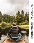 Small photo of Girl canoeing with Canoe on the lake of two rivers in the algonquin national park in ontario Canada on a cloudy day