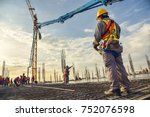 A construction worker control a pouring concrete pump on construction site and sunset background - stock photo