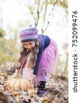 little girl picks up a pumpkin... | Shutterstock . vector #752099476
