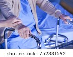 Small photo of Touching hands Asian senior or elderly old woman patient in walker with love, care, encourage and empathy at hospital