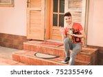 young man holding a little dog... | Shutterstock . vector #752355496