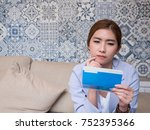 Small photo of Pretty Asian business woman looking to the saving account pass book and consideration about using the fund wisely. Investment concept, Saving Concept