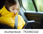 adorable girl sitting in a car... | Shutterstock . vector #752482162