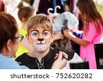 Small photo of Teacher paints face of young actor to resemble a tiger as he prepares for production