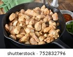 Small photo of Frying seasoned cubed chicken breasts in a cast iron skillet