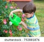 Cute Little Boy Watering Plant...