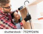 Small photo of A man and a girl add up a bookshelf for their apartment. The bookcase is made of wood. It is added by bolts. They measure the boards with a ruler.