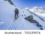 Small photo of Ski touring in high alpine landscape. Ascent and descent to a summit of an alpine peak. Snow and winter activities, skitouring in mountains.